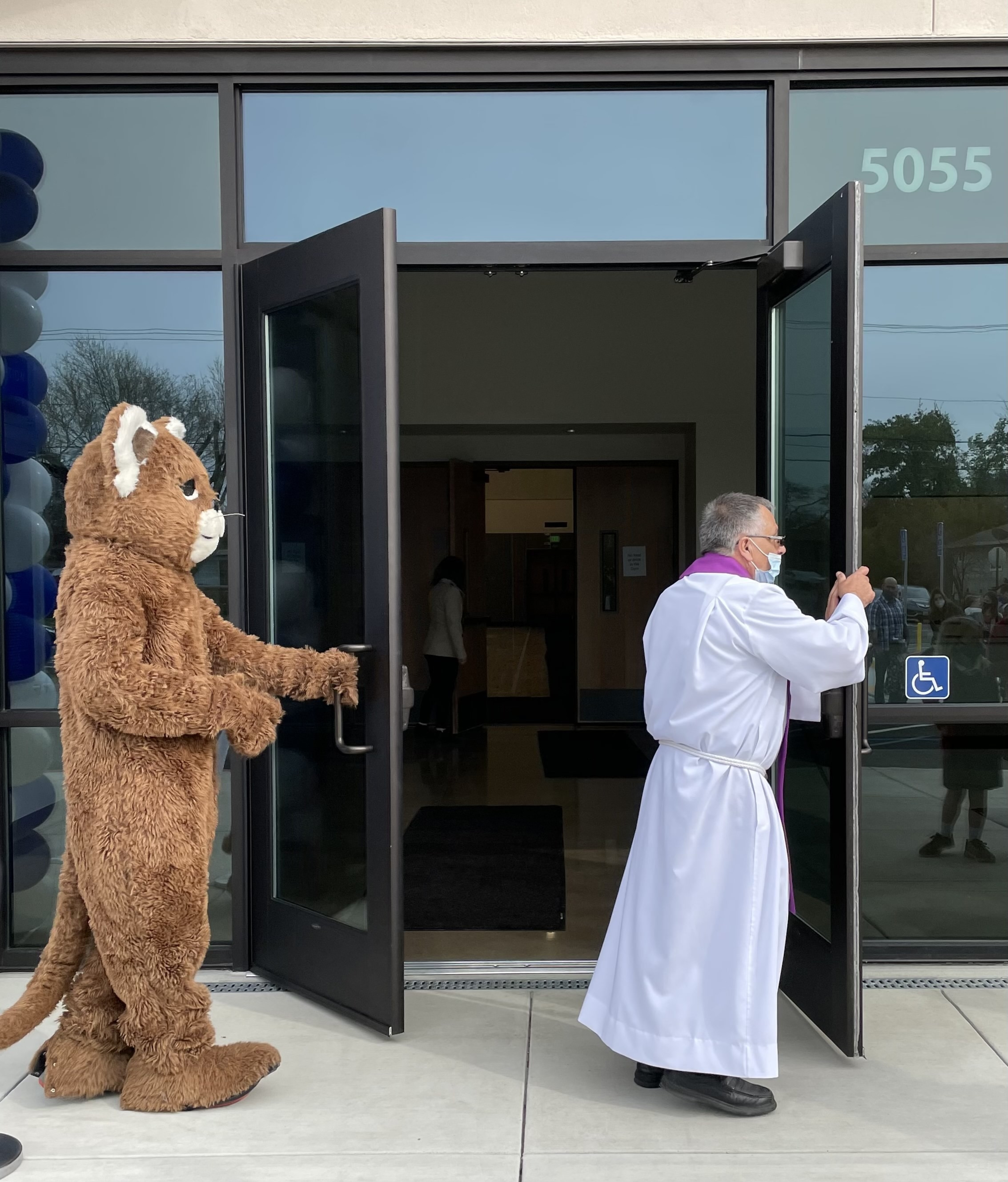 Fr. Eduino and the OLA Cougar mascot open the doors to Affinito Hall.